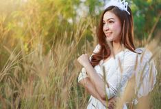 Angel woman in a grass field with sunlight. Beautiful angel woman in a grass field Royalty Free Stock Images