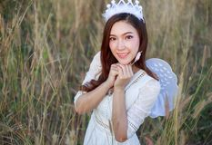 Angel woman in a grass field with sunlight. Beautiful angel woman in a grass field Royalty Free Stock Photos