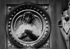 Angel and woman. Shot in black and white. Sculpture on the facade of this historic building, representing an angel and a woman. Set in Montjüic cemetery Stock Photo