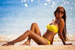Angel. yellow bikini sea. Beautiful fun joy smiling brunette woman in yellow bikini sunglasses posing tropical blue sea water has sports and tan body stock photos