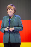 Angela Merkel holding a speech in front of the German flag Royalty Free Stock Image