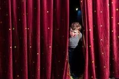 Angelägen ung skådespelare som ut ser från gardinerna Royaltyfri Fotografi