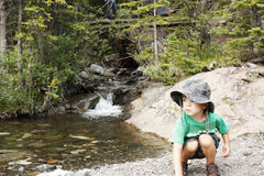Almost Angelic. A small boy crouched to pick up rocks in front of a backdrop of a small stream with a tiny waterfall in the forest Royalty Free Stock Photo