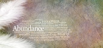 Angelic Abundance Word Cloud Banner. Two white feathers and an ABUNDANCE word cloud against a rustic subtle colored stone effect background with copy space royalty free stock image