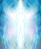 Angelic Aura Cleanse. White female silhouette figure with turquoise glow and delicate multi layered blue auric field radiating outwards with white wing-like Stock Image
