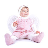 Angelic baby. Sitting in the studio isolated on white background, cute little girl wearing pink dress and feather wings, purity and innocence concept stock photography