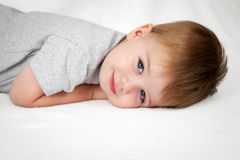 Angelic Boy. A handsome  little boy laying on his stomach with head down on a white background smiles sweetly at the camera Stock Photography