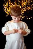 Angelic Boy Looking Down Holding seu coração imagem de stock royalty free