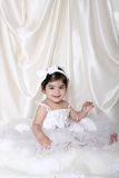 Angelic child. Picture of a 16 months old wearing a white fluffy dress with shiny satrin backdrop Stock Photo