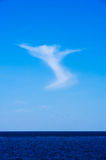 Angelic cloud ascending into blue sky from lake Royalty Free Stock Photography