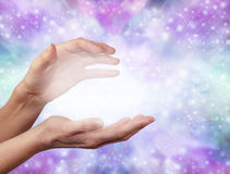 Angelic ethereal healing energy. Female hands in cupped energy sensing position with a ball of white misty light between on a sparkling glittery blue and purple Royalty Free Stock Photography