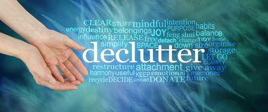 Angelic feather Declutter Word Cloud. Female cupped hands offering the word DECLUTTER surrounded by a relevant tag word cloud on a dark blue green background Royalty Free Stock Images