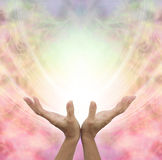 Angelic Healing Energy. Female hands outstretched sensing a beautiful pastel colored Angelic energy field with a ball of white light at the center and plenty of Royalty Free Stock Image