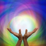 Angelic Healing Energy. Healer's outstretched hands with angelic rainbow colored background Stock Photography