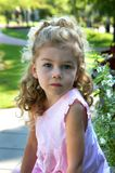 Angelic Thinker in garden. Angelic little girl looks into the camera. She is thinking and looking off into the distance. She has blond hair and ringlets stock images