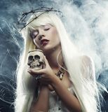 Angelic long hair woman with skull Stock Photos
