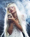 Angelic long hair woman with skull. Picture a beautiful angelic long hair woman with skull Stock Photography