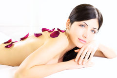 Angelic portrait of beauty with flower on naked back in white spa Stock Photo