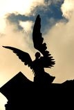 Angelic statue against troubled sky. Looking up at the silhouette of an angelic statue against a troubled sky royalty free stock image