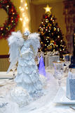 Angelic Table Setting. Christmas Eve dinner table set with angels and tree and wreath Stock Image