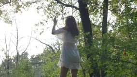 Angelic white dressed woman saluting the sun yoga relaxing in nature -. Angelic white dressed woman saluting the sun yoga relaxing in nature stock footage