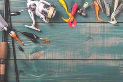 Angeln, Angelausrüstung, Spule und Fischenbojen auf grünem hölzernem Hintergrund mit freiem Raum Lizenzfreie Stockfotos