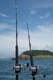 Angeln auf einem Boot über blauem Meer, Himmel und grüner Insel Stockfotografie