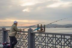 Angeln eines Mann-drei auf Galata-Brücke vor Tagesanbruch Stockfotografie