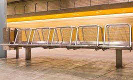 Gelber Zug, der hinter Metallsitze beschleunigt lizenzfreie stockfotos