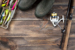 Angeln und Spule mit Stiefeln und Angelausrüstung in einem Kasten auf hölzernem Hintergrund mit freiem Raum Lizenzfreie Stockfotografie