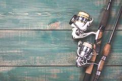 Angeln und Spulen mit Linie auf grünem hölzernem Hintergrund mit freiem Raum Getontes Bild Stockbilder