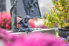 Angelo al cimitero, alla tomba con il libro aperto da ferro e ad una rosa, fiori fotografia stock
