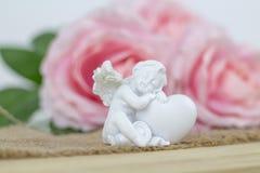 Angelo bianco Bei fiori rosa sullo scrittorio bianco Immagine Stock Libera da Diritti