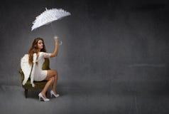 Angelo che si siede con l'ombrello bianco fotografia stock