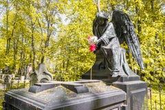 Angelo con i fiori sulla tomba Fotografie Stock Libere da Diritti