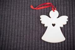Angelo di legno del mestiere su Grey Knitted Background immagine stock