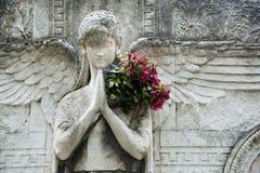 Angelo di pietra con i fiori Immagine Stock