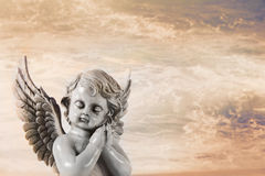 Angelo pregante triste su un fondo arancio di cielo per un condolenc Fotografie Stock