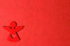 Angelo su un fondo rosso, decorazione di legno di eco, giocattolo di Natale Fotografie Stock Libere da Diritti