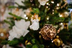 Angelo sveglio che appende e che decora un albero di Natale Immagine Stock