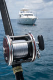Angelrute auf einem Boot über blauem Himmel und weißem Segelboot im Meer Stockfotos
