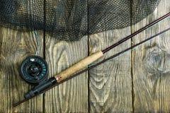 Angelrute der Fliege, flie und ein Kescher auf dem alten Holztisch Alle bereit zur Fischerei Lizenzfreie Stockfotografie