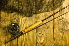 Angelrute der Fliege, flie und ein Kescher auf dem alten Holztisch Alle bereit zur Fischerei stockbilder