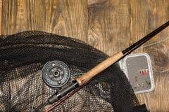 Angelrute der Fliege, flie und ein Kescher auf dem alten Holztisch Alle bereit zur Fischerei Lizenzfreie Stockfotos