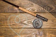 Angelrute der Fliege, flie und ein Kescher auf dem alten Holztisch Alle bereit zur Fischerei stockfoto