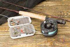 Angelrute der Fliege, flie und ein Kescher auf dem alten Holztisch Alle bereit zur Fischerei Lizenzfreies Stockfoto