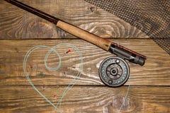 Angelrute der Fliege, flie und ein Kescher auf dem alten Holztisch Alle bereit zur Fischerei Stockbild