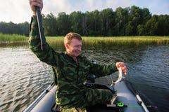 Angelrute des Fischers, zum auf dem See mit einem Gummiboot zu fischen liebhaberei lizenzfreies stockbild