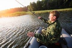 Angelrute des Fischers, zum auf dem See mit einem Gummiboot zu fischen liebhaberei stockbild