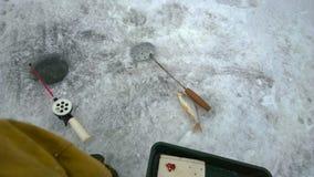 Angelrute des Winters mit Abstreicheisen und kleine Fische auf dem Eis nahe Fischenloch und -fischer ` s Bein Stockbilder